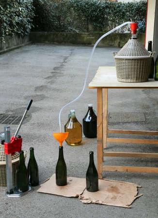 homemade bottling red wine in glass bottles with an orange funnel