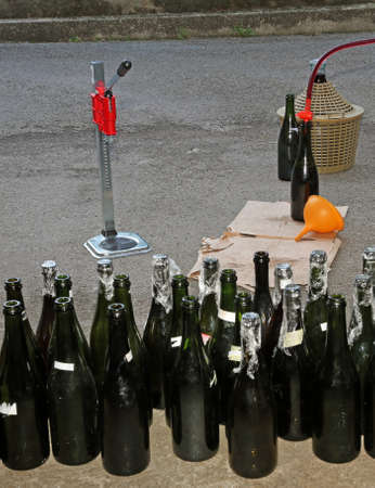 carboy: homemade bottling wine in glass bottles with an orange funnel