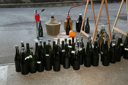 carboy: homemade bottling red wine in glass bottles with an orange funnel