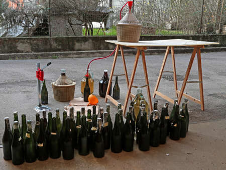 pour red wine from the demijohn to glass bottles at home