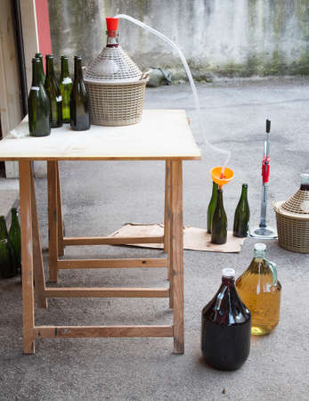 brew house: homemade wine bottling in the backyard with the Carboy and glass bottles
