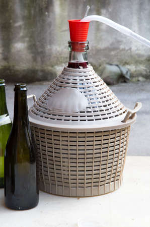 demijohn: homemade wine bottling in the backyard with the Carboy and glass bottles