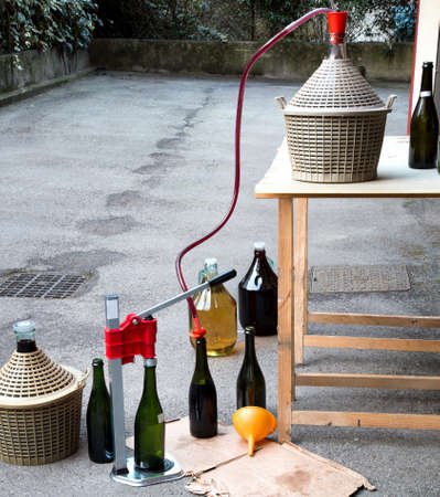 carboy: homemade wine bottling in the backyard with the Carboy and glass bottles