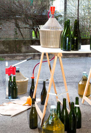 carboy: pour the wine in the backyard with the Carboy and glass bottles Stock Photo