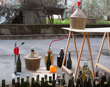 carboy: pour the wine in the backyard with the Carboy and glass bottles Editorial