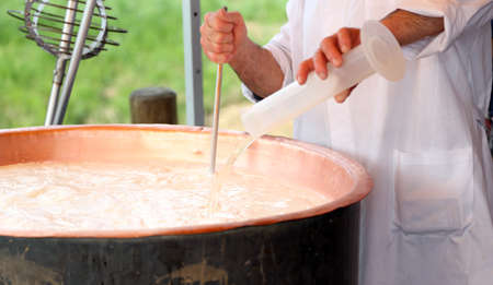 rennet: Elder Cheesemaker pours milk rennet in copper pot for making cheese in the dairy