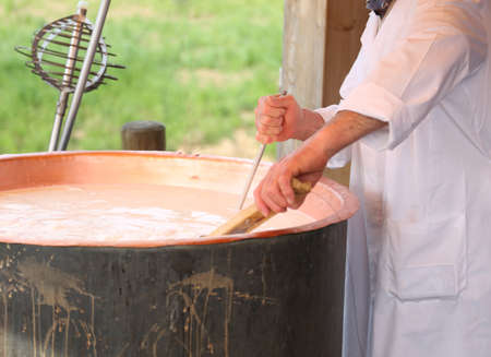 caciocavallo: expert cheesemaker checks the temperature of the boiling milk in the pot for making cheese