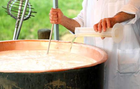 専門家 Cheesemaker は、乳製品のチーズを作るための銅鍋で牛乳のレンネットを注ぐ