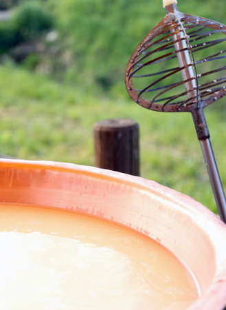 caciocavallo: Iron tool for stirring the milk in large copper pot for making cheese