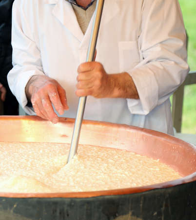 caciocavallo: expert cheesemaker boiling milk into the mixing pot for making cheese