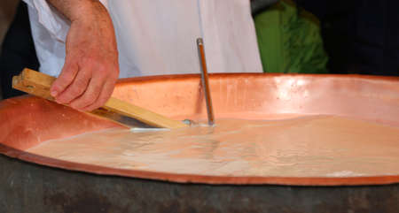 expert cheesemonger and check the temperature of the boiling milk in the pot for making cheese photo