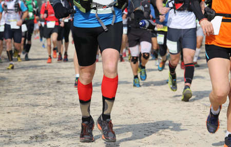 legs around: many runners racing on the road while riding in a race