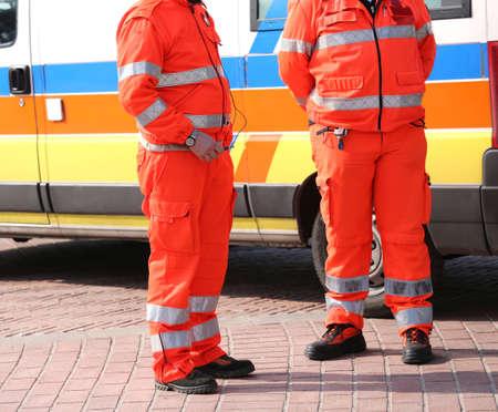 ambulancia: Uniformes anaranjados de los param�dicos de rescate de emergencia y una ambulancia Foto de archivo