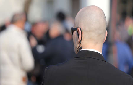 private security: bald security guard with the headset to control people Stock Photo