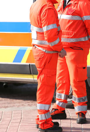 paramedics: Orange uniforms of the paramedics for emergency rescue and an ambulance