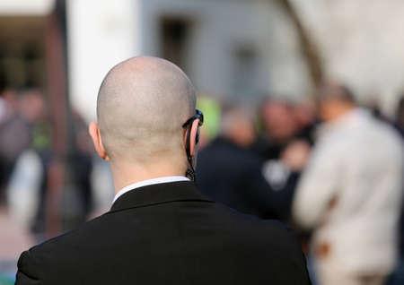 guardaespaldas: guardia de seguridad con gafas oscuras y un auricular de radio para controlar a la gente