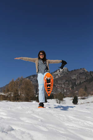 Beautiful smiling woman with snowshoes in winter in snowy mountain photo