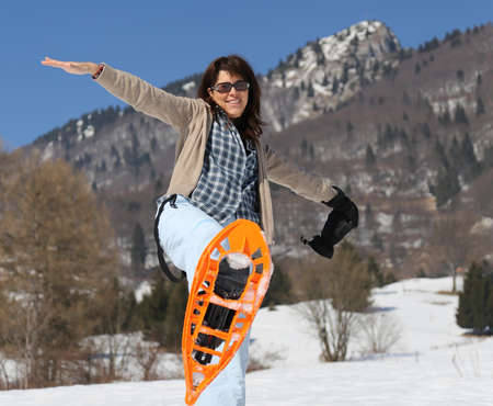 Nice woman with snowshoes in winter in snowy mountain photo
