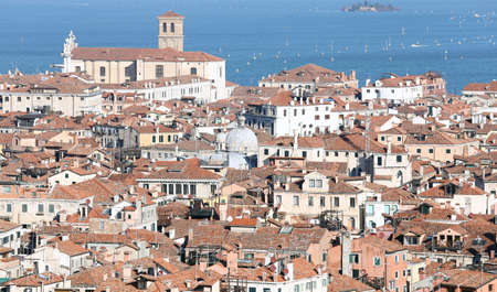 overpopulation: Venice, Italy, red-tiled roofs of the houses and the Church by the sea