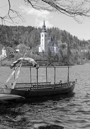 black moor: rowboats moored on the shore of Lake Bled in Slovenia and the Church on the island in black and white Stock Photo