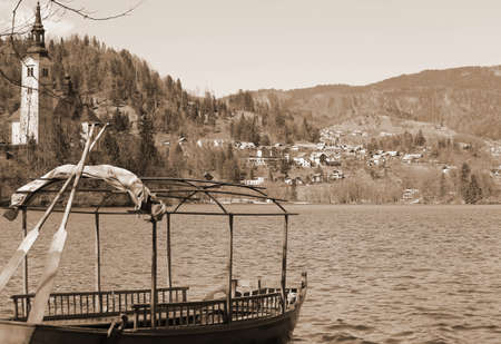 rowboats: rowboats moored on the shore of Lake Bled in Slovenia and the Church on the island sepia style