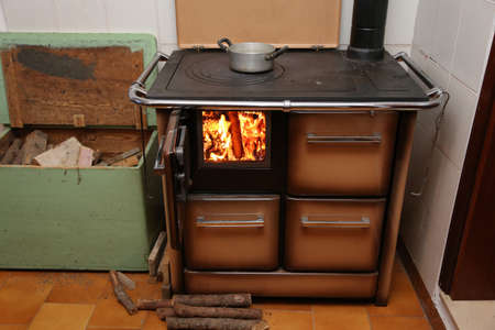 woodburning: stove a wood-burning Stove with fire lit in the old mountain home Stock Photo