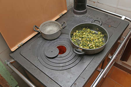 woodburning: pan with zucchini baked in cast iron stove with fire lit in the old mountain home