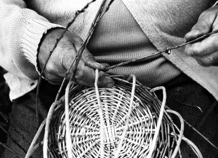 laborious hands of elder craftsmen create a woven wicker basket