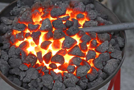 ferrous foundry: glowing lava in the grate of the blacksmith during the making of the piece of iron