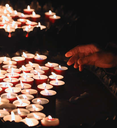 lit collection: hand of an elderly woman lights a candle to pray during mass at Church Stock Photo