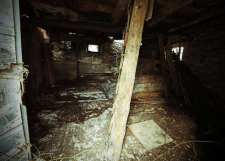 derrumbe: abandonada casa en ruinas con peligro de derrumbe y una vieja escalera de madera