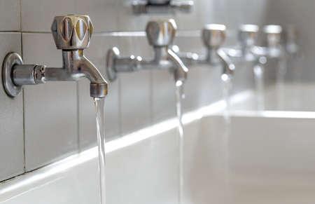 beber agua: Muchos grifos de acero con el agua potable que fluye en el baño de la universidad Foto de archivo