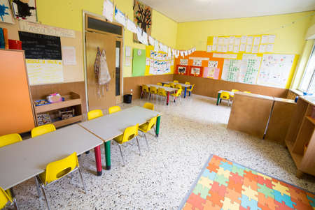 Classromm of kindergarten with tables and small yellow chairs for children photo