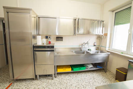 Large industrial kitchen with refrigerator, dishwasher and sink all stainless steel Imagens