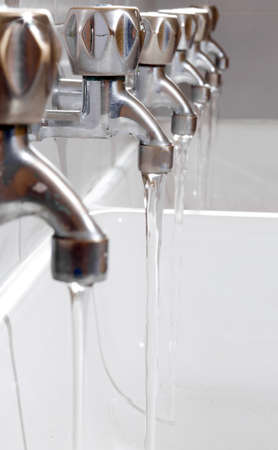 many steel taps with drinking water flowing in college bathroom photo