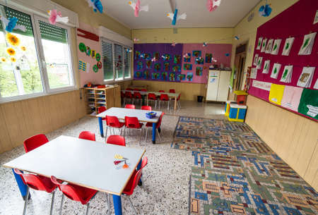 go inside: In a nursery class with tables and small red chairs for children