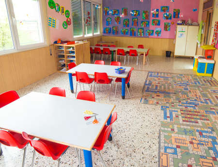 classroom: classromm of kindergarten with tables and small red chairs for children