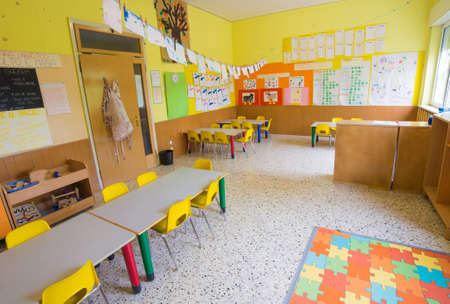 classromm of kindergarten with tables and small yellow chairs for children
