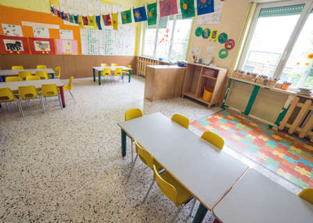 go inside: classromm of kindergarten with tables and small yellow chairs for children