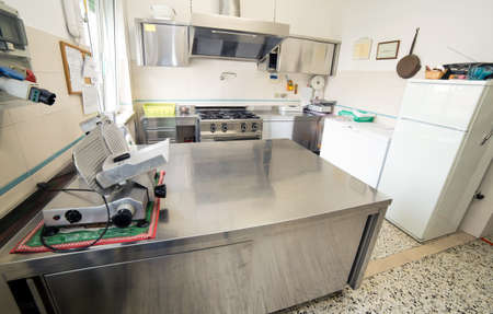 huge stainless steel kitchen with gas stove and an industrial meat slicer photo