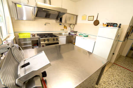 huge stainless steel kitchen with gas stove and a meat slicer Stock Photo