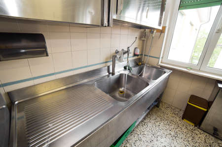 industrial kitchen: huge sink stainless steel industrial kitchen with open tap Stock Photo