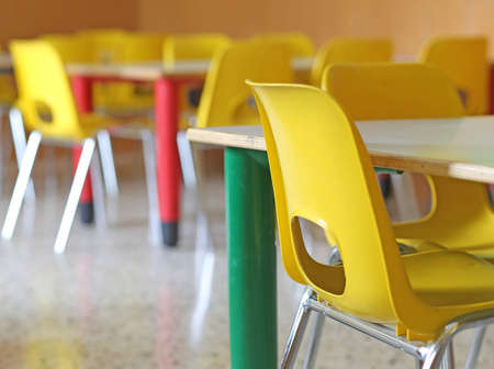 Classroom with yellow chairs and tables in the kindergarten photo