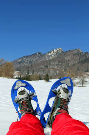 excursions: Mountaineers legs with snowshoes for excursions in the mountains
