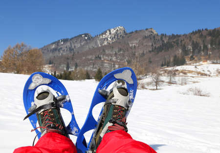 excursions: Mountaineers legs with snowshoes for excursions on the snow in the mountains