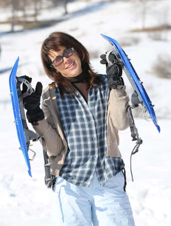 snowshoes: Pretty woman with snowshoes in the mountains