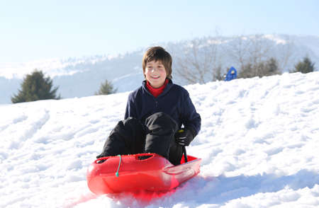 bob: cute kid with brown hair in the winter plays with bob in the mountains Stock Photo