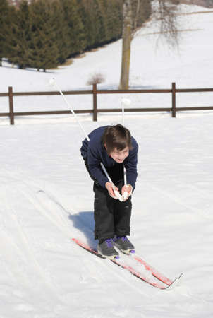 crosscountry: pretty young boy goes on cross-country skis on the white snow in the mountains in winter Stock Photo