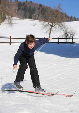 skiing accident: inexperienced boy trying the cross-country skiing and then falls on snow Stock Photo