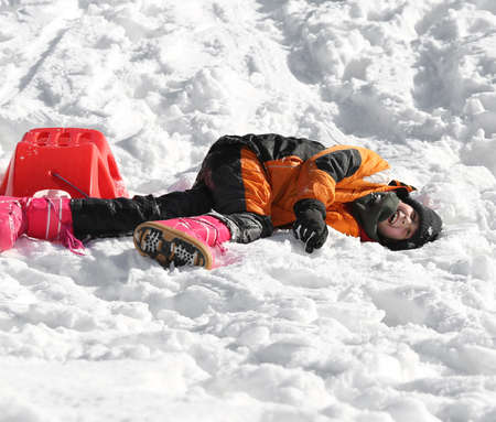 skiing accident: little boy falls from red sleigh in the mountains in winter Stock Photo